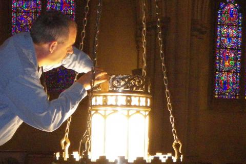 Facilities Operations employees lighting a chandelier