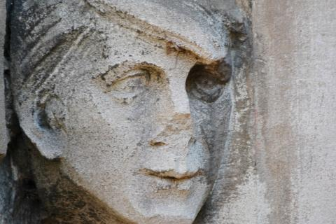 Detail photo of a face carved into stone